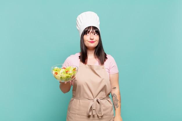 Jonge chef-kokvrouw die haar schouders ophaalt, zich verward en onzeker voelt, twijfelt met gekruiste armen en een verbaasde blik