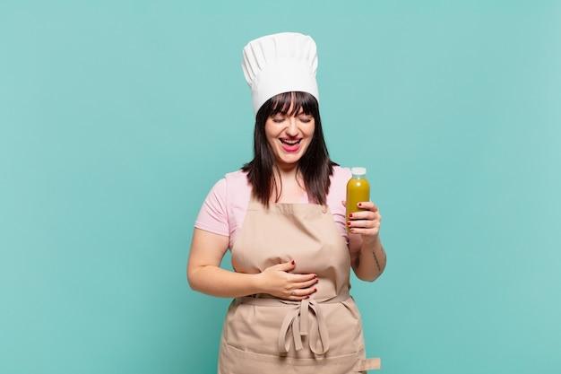 Jonge chef-kokvrouw die hardop lacht om een hilarische grap, zich gelukkig en opgewekt voelt, plezier heeft