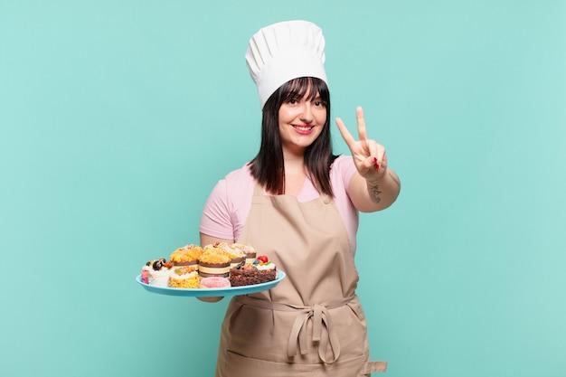 Jonge chef-kokvrouw die lacht en er gelukkig, zorgeloos en positief uitziet, gebarend overwinning of vrede met één hand