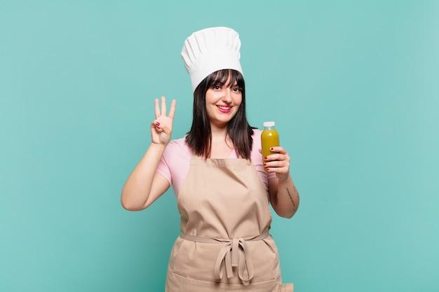Jonge chef-kokvrouw die lacht en er vriendelijk uitziet, nummer drie of derde toont met de hand naar voren, aftellend