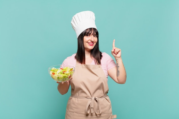 Jonge chef-kokvrouw die lacht en er vriendelijk uitziet, nummer één toont of eerst met de hand naar voren, aftellend