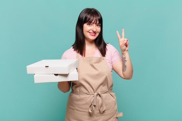 Jonge chef-kokvrouw die lacht en er vriendelijk uitziet, nummer twee of seconde toont met de hand naar voren, aftellend