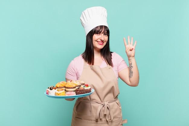 Jonge chef-kokvrouw die lacht en er vriendelijk uitziet, nummer vier of vierde toont met de hand naar voren, aftellend
