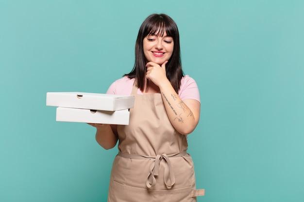 Jonge chef-kokvrouw die lacht met een gelukkige, zelfverzekerde uitdrukking met de hand op de kin, zich afvragend en opzij kijkend