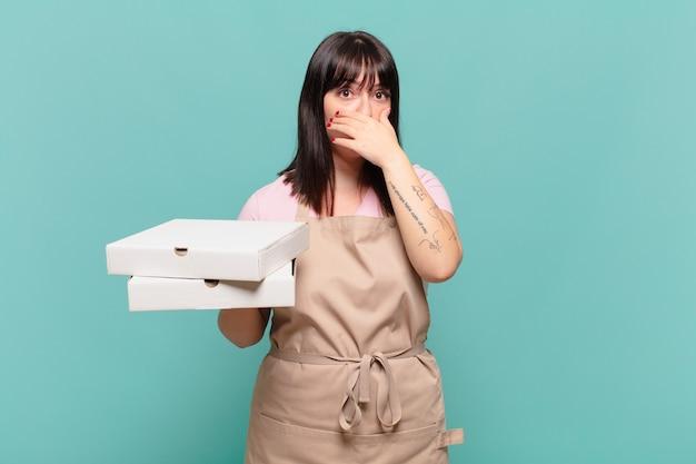 Jonge chef-kokvrouw die mond bedekt met handen met een geschokte, verbaasde uitdrukking, een geheim houdt of oeps zegt