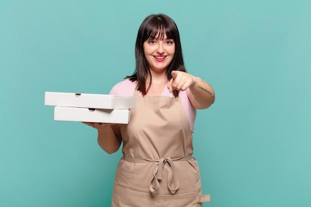 Jonge chef-kokvrouw die naar de camera wijst met een tevreden, zelfverzekerde, vriendelijke glimlach, die jou kiest