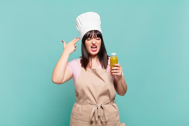 Jonge chef-kokvrouw die ongelukkig en gestrest kijkt, zelfmoordgebaar maakt pistoolteken met hand, wijzend naar hoofd