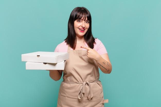 Jonge chef-kokvrouw die opgewonden en verrast kijkt en naar de zijkant en naar boven wijst om ruimte te kopiëren