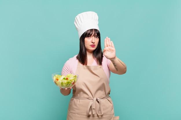Jonge chef-kokvrouw die serieus, streng, ontevreden en boos kijkt en een open palm toont die een stopgebaar maakt