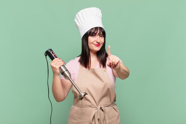 Jonge chef-kokvrouw die trots en zelfverzekerd glimlacht en nummer één triomfantelijk poseert, voelt zich een leider