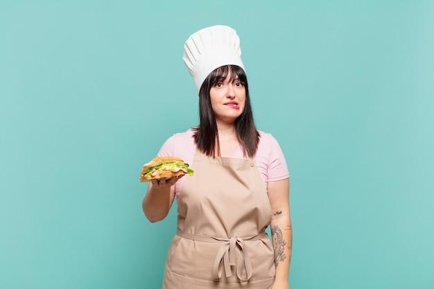 Jonge chef-kokvrouw die verbaasd en verward kijkt, lip bijt met een nerveus gebaar, niet wetend het antwoord op het probleem