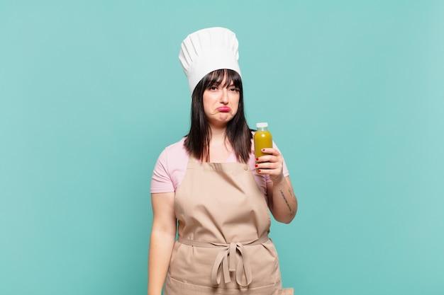 Jonge chef-kokvrouw die verdrietig en zeurt met een ongelukkige blik, huilt met een negatieve en gefrustreerde houding