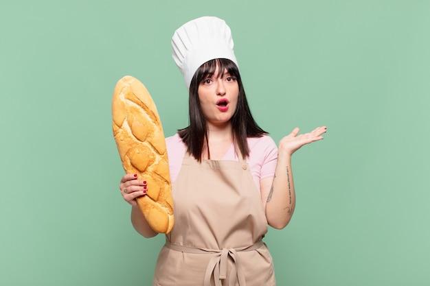 Jonge chef-kokvrouw die verrast en geschokt kijkt, met open mond terwijl ze een object vasthoudt met een open hand aan de zijkant
