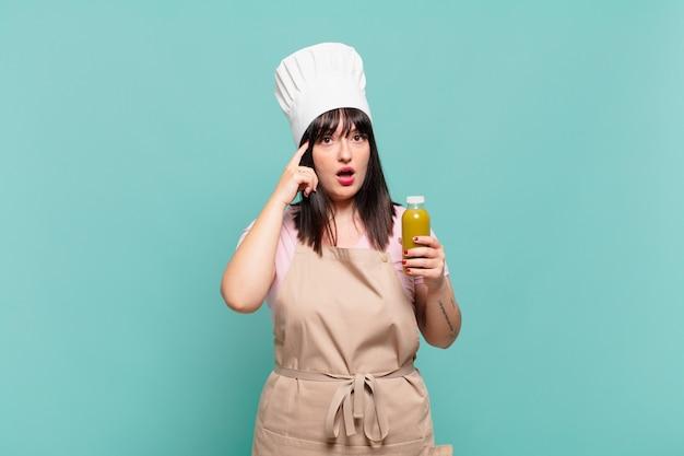 Jonge chef-kokvrouw die verrast, met open mond, geschokt kijkt en een nieuwe gedachte, idee of concept realiseert