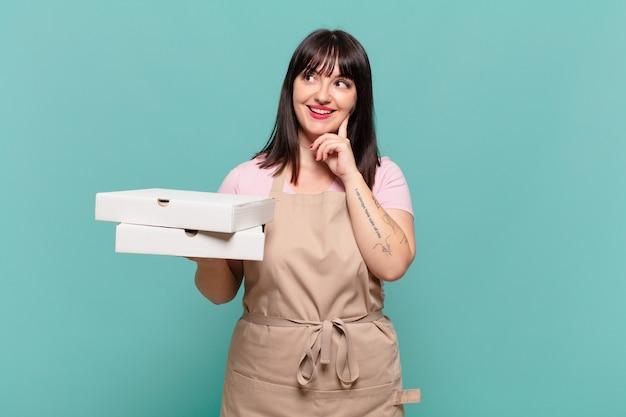 Jonge chef-kokvrouw die vrolijk lacht en dagdroomt of twijfelt, opzij kijkend
