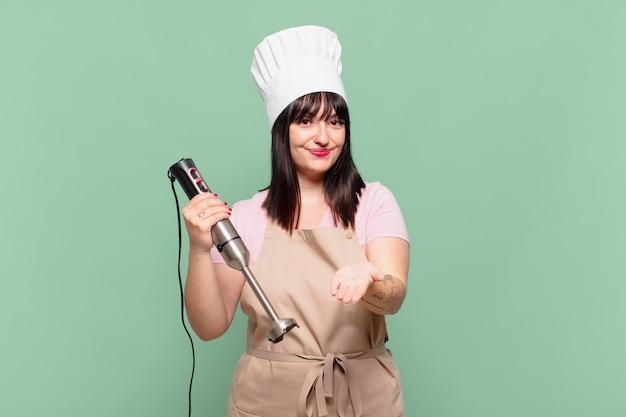 Jonge chef-kokvrouw die vrolijk lacht met een vriendelijke, zelfverzekerde, positieve blik, een object of concept aanbiedt en toont