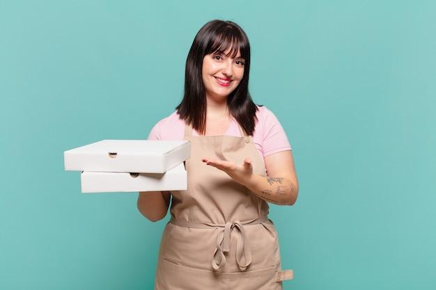 Jonge chef-kokvrouw die vrolijk lacht, zich gelukkig voelt en een concept toont in kopieerruimte met handpalm