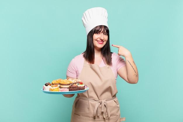 Jonge chef-kokvrouw die zelfverzekerd glimlacht en wijst naar een brede glimlach, een positieve, ontspannen, tevreden houding