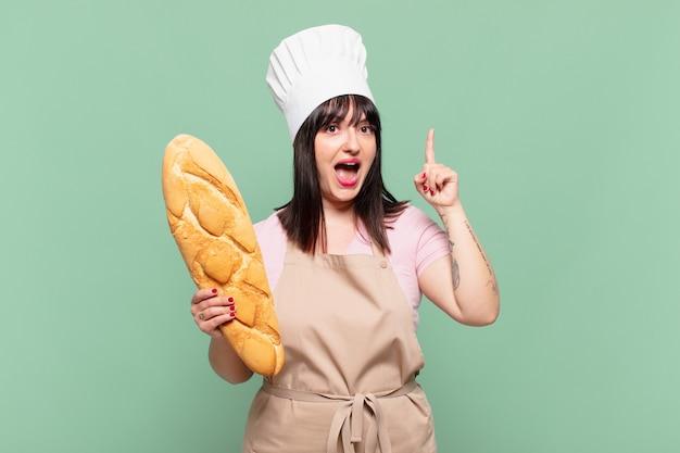 Jonge chef-kokvrouw die zich een gelukkig en opgewonden genie voelt na het realiseren van een idee, vrolijk vinger opstekend, eureka!