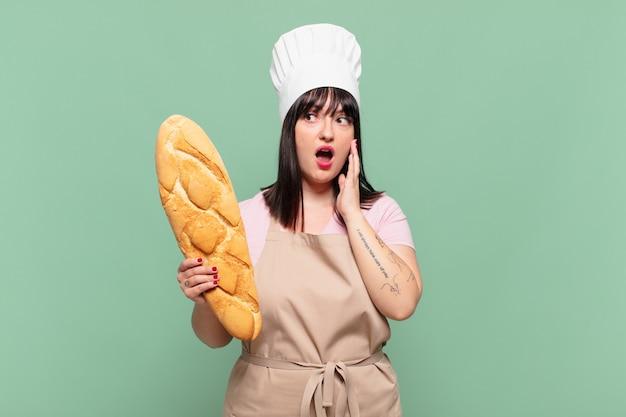 Jonge chef-kokvrouw die zich gelukkig, opgewonden en verrast voelt, opzij kijkend met beide handen op het gezicht