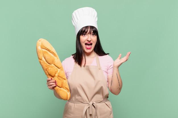 Jonge chef-kokvrouw die zich gelukkig, opgewonden, verrast of geschokt voelt, glimlacht en verbaasd over iets ongelooflijks