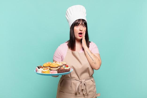 Jonge chef-kokvrouw die zich geschokt en bang voelt, doodsbang kijkt met open mond en handen op de wangen