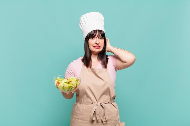 Jonge chef-kokvrouw die zich gestrest, bezorgd, angstig of bang voelt, met de handen op het hoofd, in paniek bij vergissing