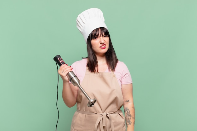 Jonge chef-kokvrouw die zich verbaasd en verward voelt, met een stomme, verbijsterde uitdrukking die naar iets onverwachts kijkt