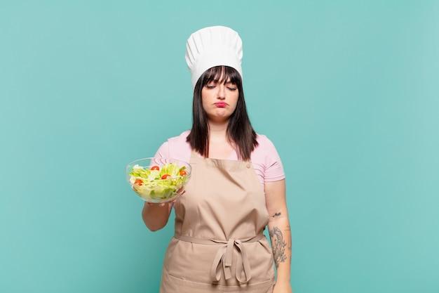 Jonge chef-kokvrouw die zich verdrietig, overstuur of boos voelt en opzij kijkt met een negatieve houding, fronsend in onenigheid