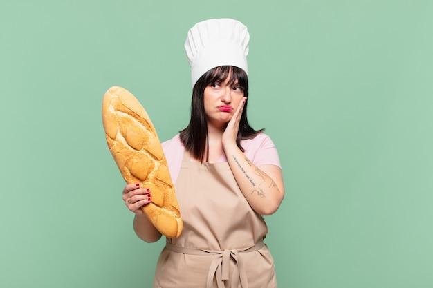 Jonge chef-kokvrouw die zich verveeld, gefrustreerd en slaperig voelt na een vermoeiende, saaie en vervelende taak, haar gezicht met de hand vasthoudend