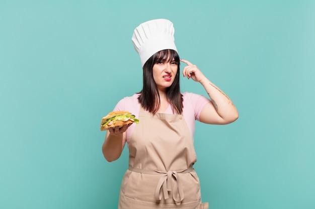 Jonge chef-kokvrouw die zich verward en verbaasd voelt en laat zien dat je gek, gek of gek bent