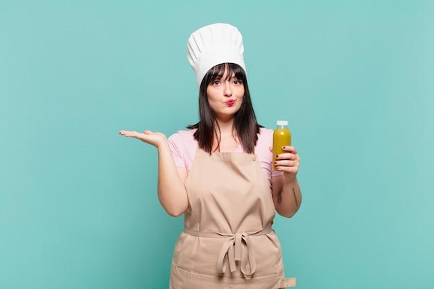 Jonge chef-kokvrouw die zich verward en verward voelt, twijfelt, weegt of verschillende opties kiest met grappige uitdrukking