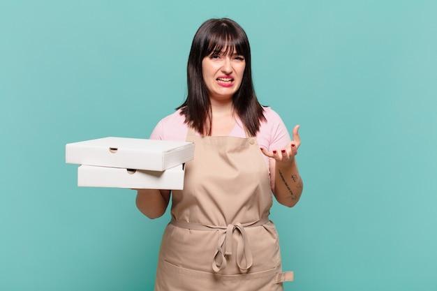Jonge chef-kokvrouw kijkt boos, geïrriteerd en gefrustreerd schreeuwend wtf of wat is er mis met jou?