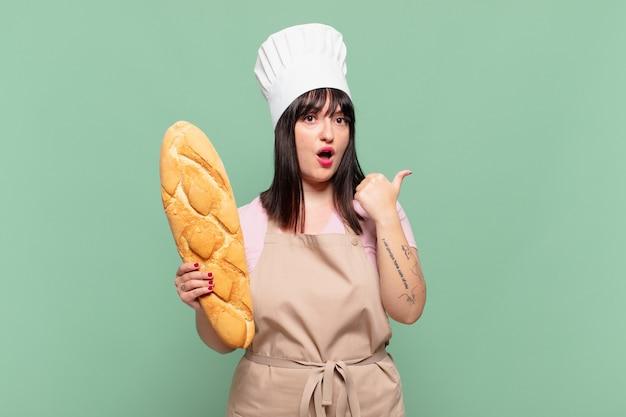 Jonge chef-kokvrouw kijkt verbaasd in ongeloof, wijst naar een object aan de zijkant en zegt wow, ongelooflijk