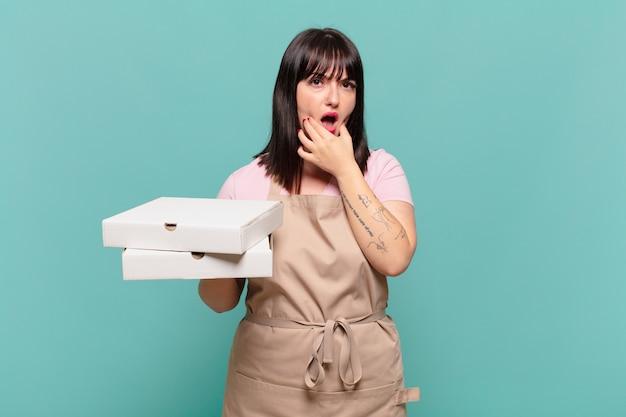 Jonge chef-kokvrouw met wijd open mond en ogen en hand op kin, onaangenaam geschokt, wat zeggend of wauw
