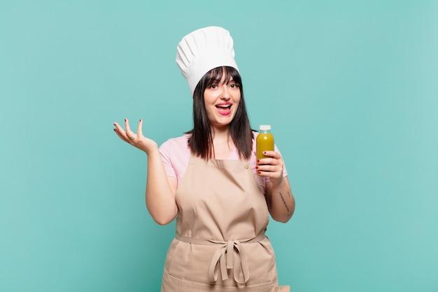 Jonge chef-kokvrouw voelt zich gelukkig, verrast en opgewekt, glimlacht met een positieve houding, realiseert een oplossing of idee