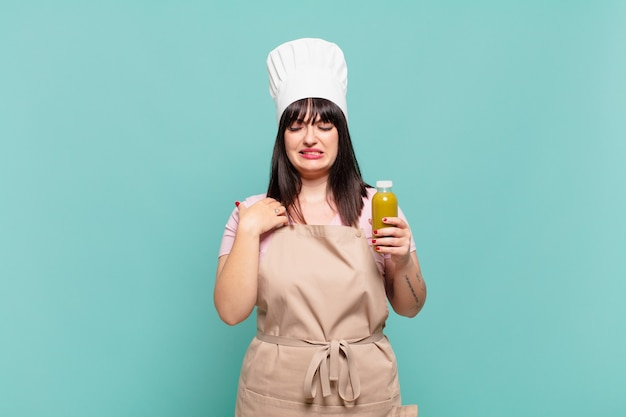 Jonge chef-kokvrouw voelt zich gestrest, angstig, moe en gefrustreerd, trekt aan de nek van het shirt, ziet er gefrustreerd uit met een probleem
