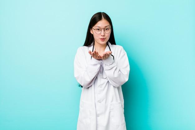 Jonge chinese artsenvrouw die lippen vouwt en palmen houdt om luchtkus te verzenden.