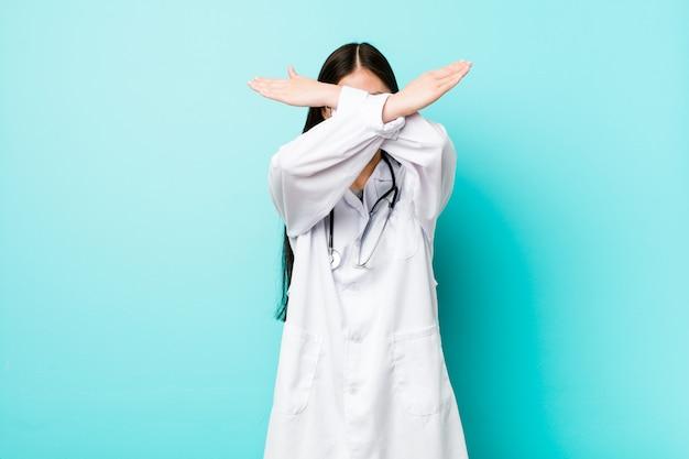 Jonge chinese artsenvrouw die twee wapens gekruist houdt, ontkenning.