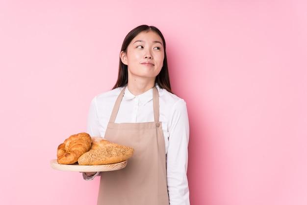 Jonge chinese bakkersvrouw geïsoleerde dromen van het bereiken van doelstellingen en doeleinden