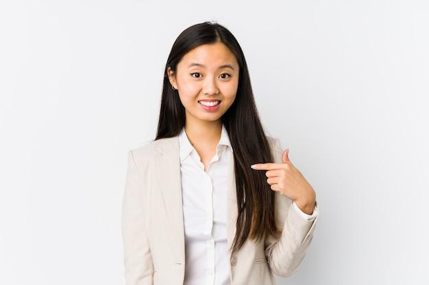 Jonge chinese bedrijfsvrouw geïsoleerde persoon die met de hand naar een ruimte van het overhemdsexemplaar richten, trots en zeker