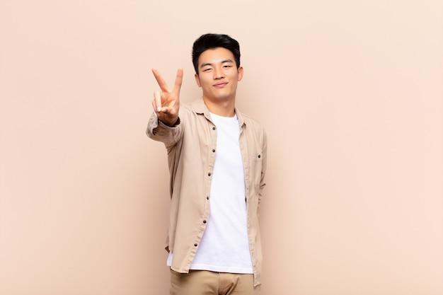 Jonge chinese en mens die gelukkige, onbezorgde en positieve, gesturing overwinning of vrede met één hand glimlachen kijken tegen vlakke kleurenmuur