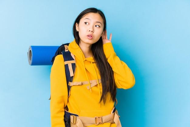 Jonge chinese geïsoleerde backpackervrouw die een roddel probeert te luisteren.