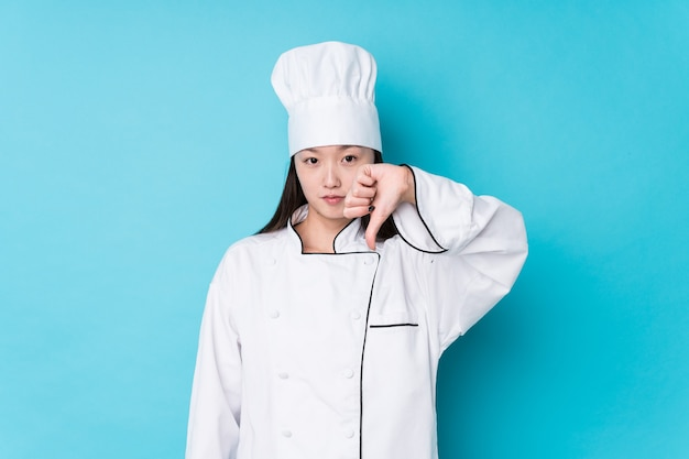 Jonge chinese geïsoleerde chef-kokvrouw met een afkeergebaar, duimen naar beneden. meningsverschil concept.