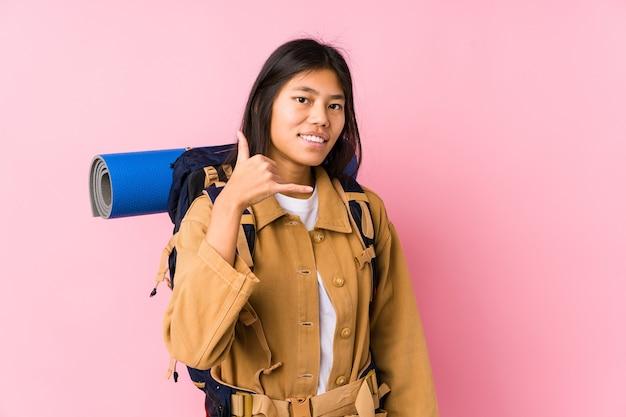 Jonge chinese geïsoleerde reizigersvrouw tonend een mobiel telefoongesprekgebaar met vingers.