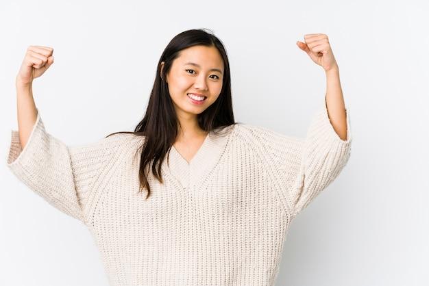 Jonge chinese geïsoleerde vrouw die krachtgebaar met wapens toont, symbool van vrouwelijke macht