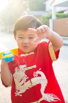 Jonge chinese jongen glimlachend en gelukkig in chinese nieuwjaarskostuumjurk