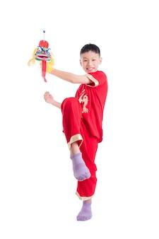 Jonge chinese jongen in rode kleuren traditionele kleding die chinese leeuwmarionet spelen