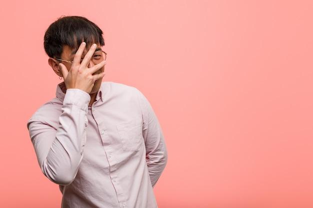 Jonge chinese man beschaamd en lachen op hetzelfde moment
