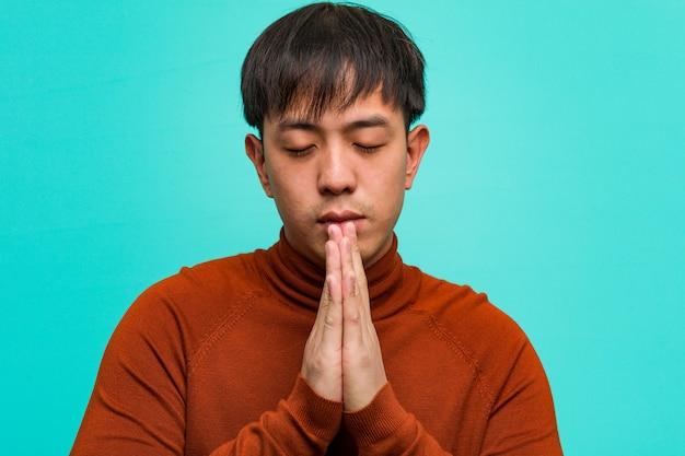 Jonge chinese man bidden erg blij en zelfverzekerd